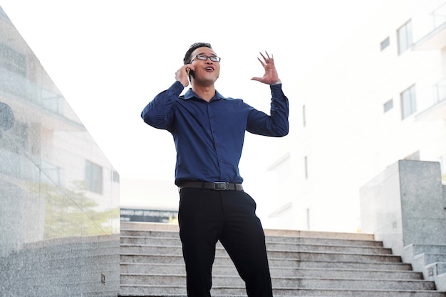 Excited businessman talking on phone