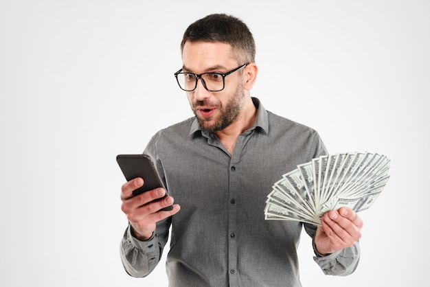 Excited businessman using mobile phone holding money.