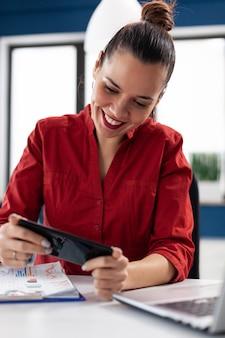 Возбужденная деловая женщина развлекается на работе, играя в видеоигры