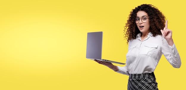 노트북 컴퓨터를 들고 손가락을 가리키는 흰색 셔츠에 흥분된 사업가 노란색 배경 위에 절연