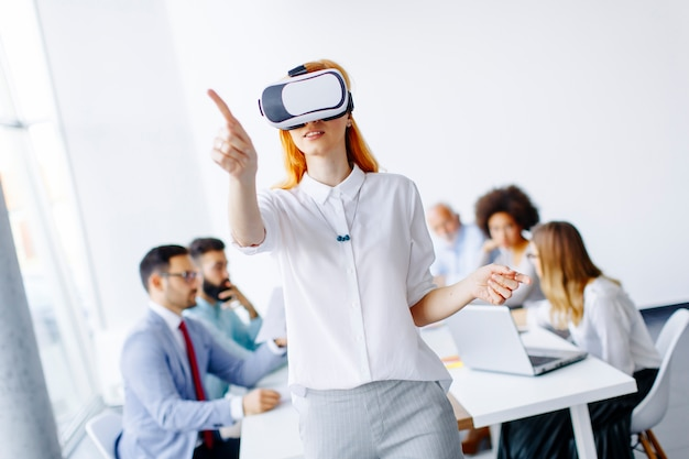 Excited businesswoman in virtual reality glasses trying to touch cyber objects