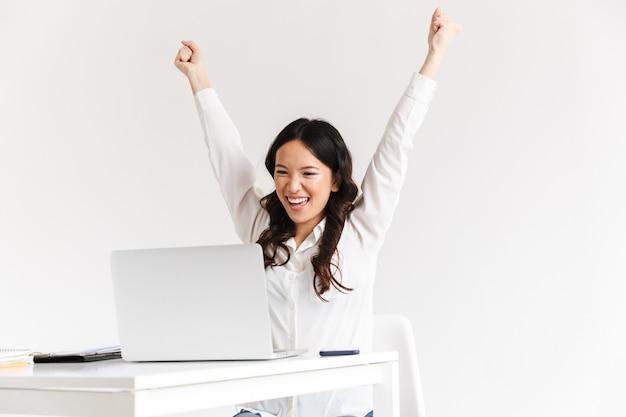 Возбужденная деловая женщина с длинными темными волосами кричит с поднятыми руками и празднует успех во время работы в офисе