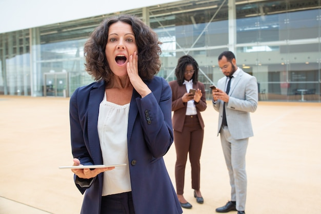 Excited businesswoman with tablet getting great shocking news