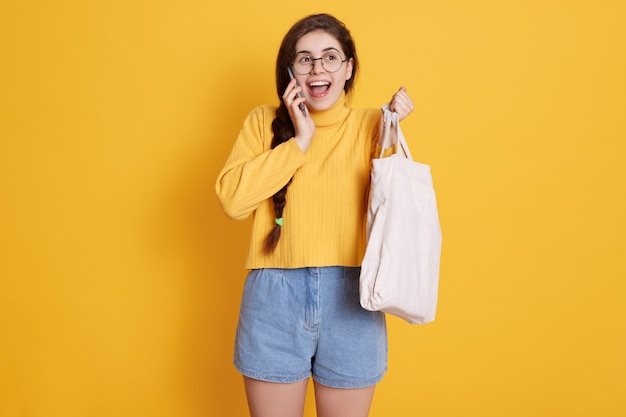 세련된 스웨터, 짧은 안경을 쓰고 입을 크게 벌리고, 전화로 이야기하는 손에 가방을 가진 흥분된 구매자 소녀