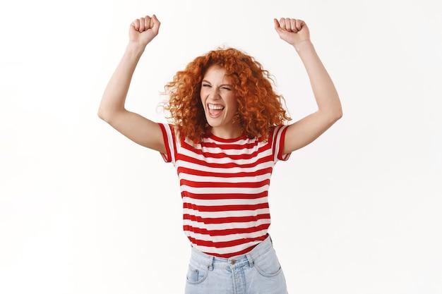 興奮したのんきな赤毛生意気な縮れ毛の女性ジャンプダンス楽しんで叫んで一緒に歌う音楽バンドコンサートを楽しむ手を上げる勝利勝利ジェスチャー叫ぶええ