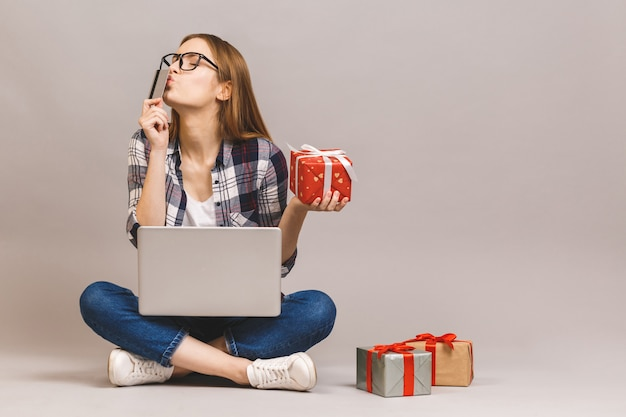 An excited casual girl holding laptop computer and credit card while sitting on a floor with stack of gift boxes