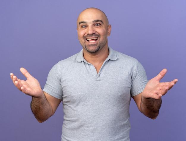 紫色の壁に隔離された空の手を示す正面を見て興奮したカジュアルな中年男性