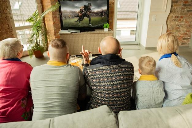 アメリカンフットボールのチャンピオンシップ、自宅でのスポーツの試合を見ている興奮した白人家族。祖父母、両親、そして子供がお気に入りの代表チームを応援しています。感情、サポート、一体感の概念。 Premium写真
