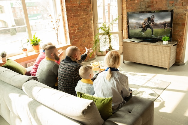 Excited caucasian family watching american football championship, sport match at home. grandparents, parents and kid cheering for favourite national team. concept of emotions, support, togetherness.