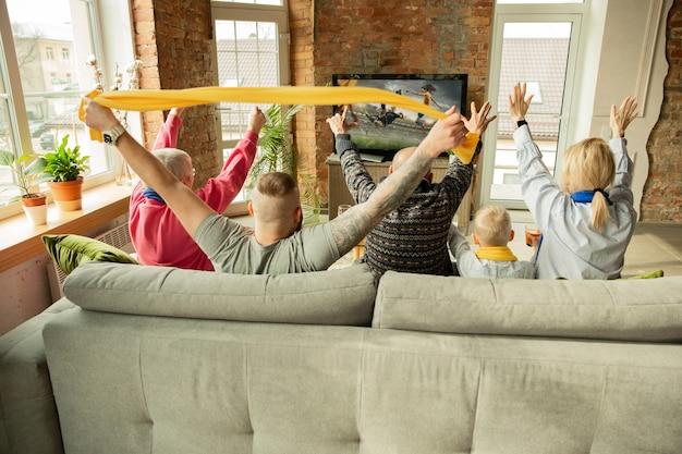 집에서 여자 축구 선수권 대회 스포츠 경기를 보고 흥분한 백인 가족