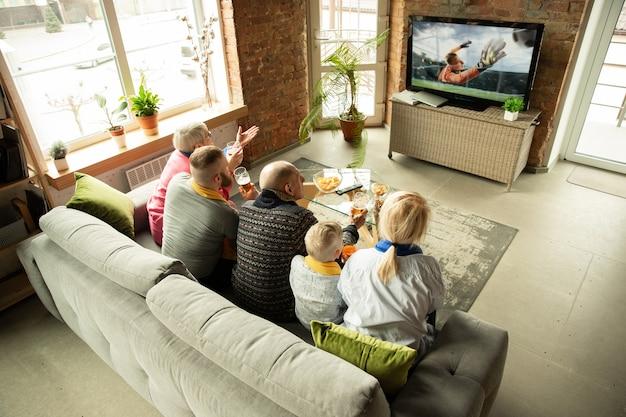 自宅でサッカー、サッカースポーツの試合を見ている興奮した白人家族。祖父母、両親、そして子供がお気に入りの代表チームを応援しています。人間の感情、サポート、一体感の概念。