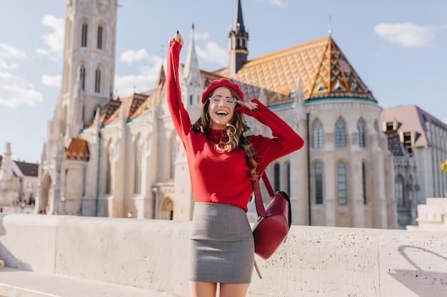 Eccitata ragazza caucasica in abito glamour in posa emotivamente vicino al vecchio bellissimo palazzo