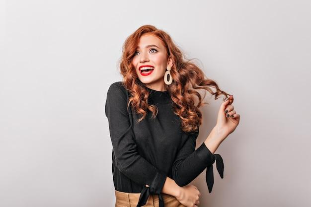 彼女の生姜の髪で遊んでいる黒いブラウスの興奮した白人の女の子。魅力的な若い女性は金色のイヤリングを着ています。