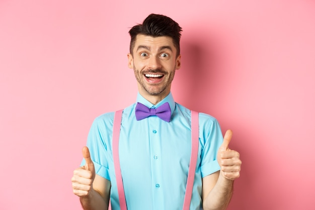 Excited caucasian guy showing thumbs up and praising great work, well done gesture, standing in suspenders and bow-tie on pink background.