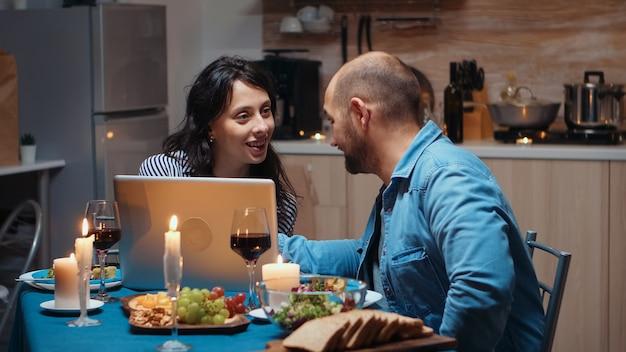 Возбужденные кавказские пара любовника обедают вместе и с помощью ноутбука. взрослые сидят за столом, ищут, просматривают, серфят, используют технологии, наслаждаются едой в столовой