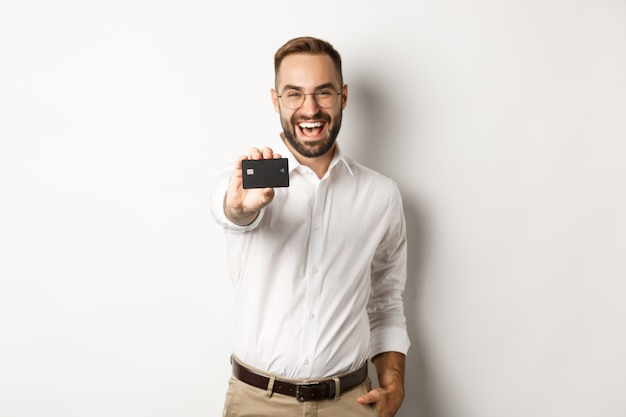 Excited caucasian man in glasses showing credit card, concept of shopping.
