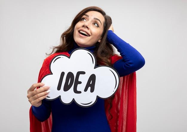 La ragazza caucasica eccitata del supereroe con il mantello rosso mette la mano sulla testa e tiene la bolla di idea che esamina il lato isolato sulla parete bianca con lo spazio della copia