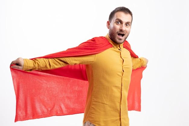 흥분된 백인 슈퍼 히어로 남자는 복사 공간이 흰 벽에 고립 된 빨간 망토를 들고 팔을 열어 유지 약자
