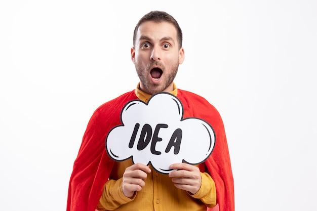 赤いマントを着た興奮した白人のスーパーヒーローがアイデアバブルを保持している