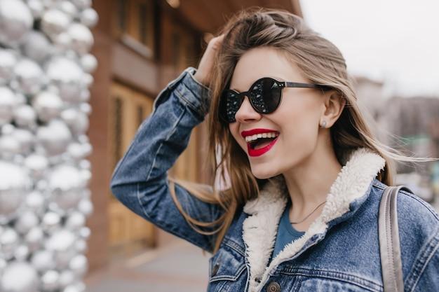 Возбужденная кавказская женщина в модных солнцезащитных очках смотрит в сторону с удивленной улыбкой. снимок приятного гитл в джинсовой куртке, смеющегося на выходных.