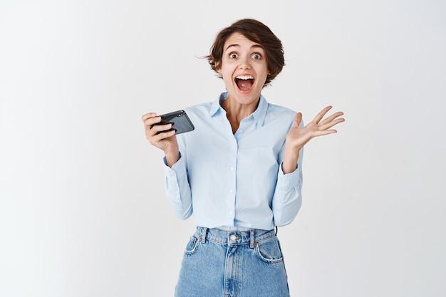 幸せと驚きを叫び、携帯電話を持って勝利し、オンラインまたはビデオゲームで勝つ、白い壁に興奮した白人女性