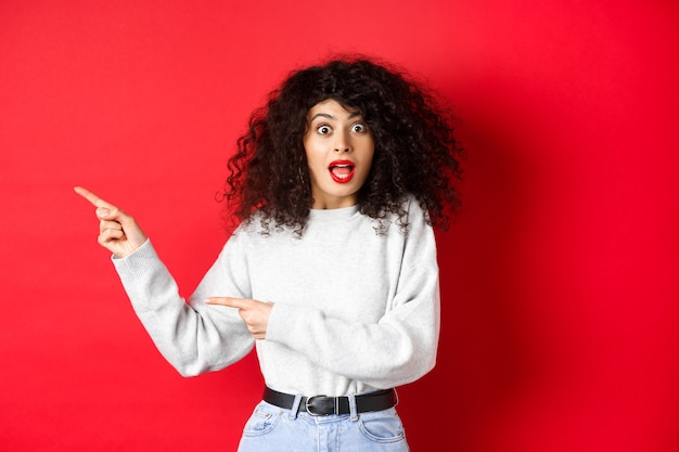 Excited caucasian woman in sweatshirt, checking out banner, pointing fingers left at empty space, showing advertisement, red background.