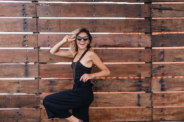 Eccitata donna caucasica in occhiali da sole alla moda danza divertente. foto all'aperto del bellissimo modello femminile biondo isolato sulla parete di legno.