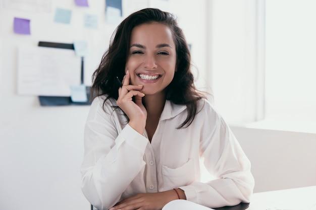 갈색 머리를 가진 흥분된 백인 여자는 행복감을 느끼고 카메라를보고 책상에 앉아