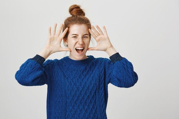 笑顔と顔の近くに手を示す興奮したカリスマ的な赤毛の女性