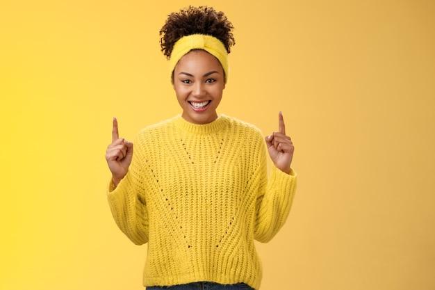 Eccitato affascinante giovane ragazza afro-americana acconciatura afro in fascia maglione che punta verso l'alto le dita indice sorridendo ridacchiando chiedendo di acquistare il fidanzato fantastico cosmetici b-day presente.