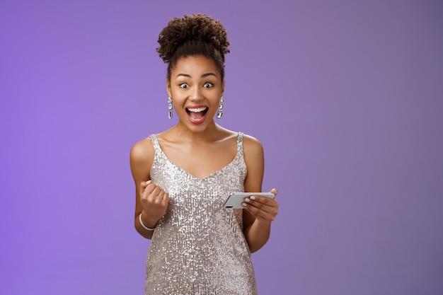 Eccitato affascinante giovane donna afro-americana fortunata gioco vincente che gioca smartphone in piedi contento urlando felicemente stringendo il pugno trionfando con gioia celebrando la grande notizia ricevuta messaggio.