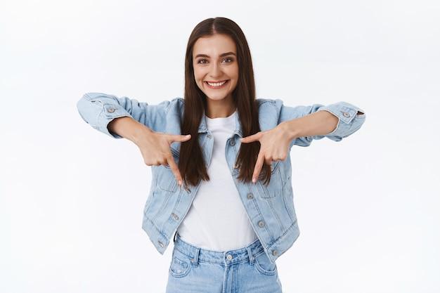 クールなプロモーションを下向きに見せて、秋のセール中に何を買うか、何かをお勧めし、リンクを宣伝し、白い背景にアドバイスを与えるように下向きに笑って、興奮した陽気な魅力的なブルネットの女の子