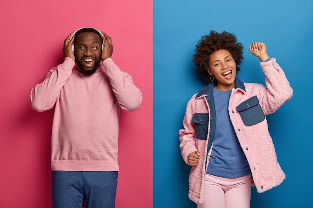 Excited cheerful black man and his girlfriend have fun on disco floor, dance to rhythm of music, wear wireless headphones, chilling and vibing indoor, spend free time at awesome party or festival