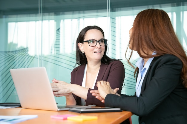 Excited cheerful businesswomen discussing project while sitting at open laptop