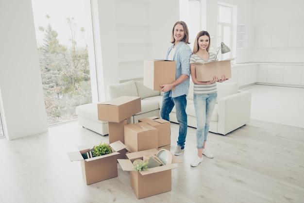 Взволнованная веселая пара открывает картонные коробки