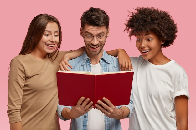 Excited cheerful curious multiethnic two young women and handsome guy look at textbook, read information, isolated over pink wall. happy interracial students learn something before exam
