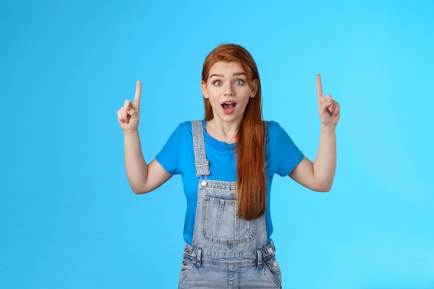 Excited cheerful cute ginger girl 20s, open mouth entertained, look enthusiastic amazed, pointing up, top copy space, promote excellent awesome new product, stand blue background astonished
