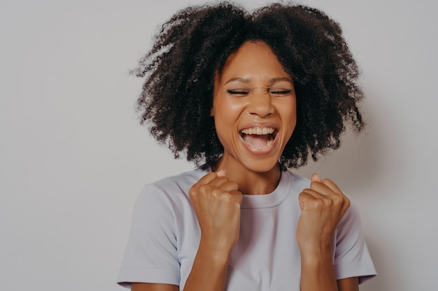 Excited cheerful dark skinned girl clenches fists while closed her eyes exclaims with victory or willing to win, excited female dressed in casual wear shouts yeah, isolated on white