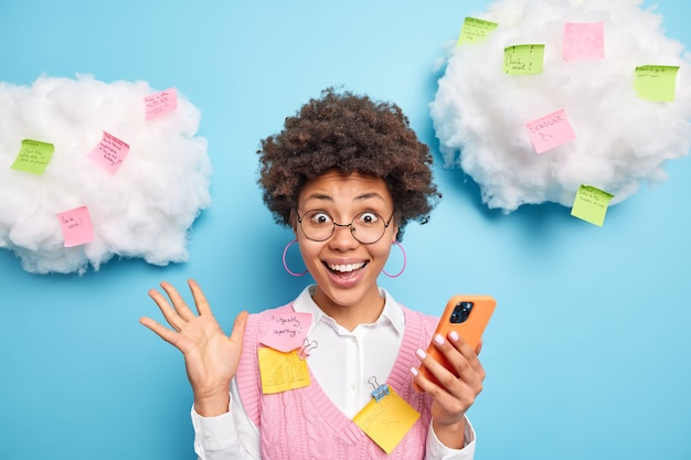 Excited cheerful diligent student holds smartphone finds out excellent results of passed exam smiles broadly poses against blue wall with pasted colorful stickers on clouds