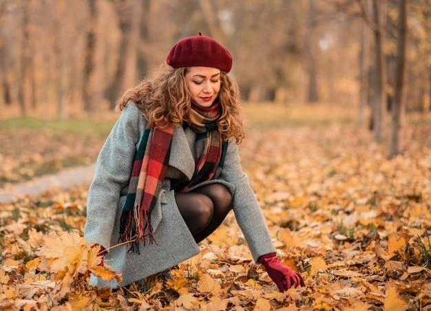 興奮した陽気な女の子が葉を落とし、美しい秋の色で楽しい。公園で紅葉を保持している美しい笑顔の女の子のクローズアップの肖像画。秋の気分