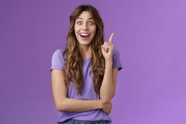 흥분된 쾌활한 행복한 창조적 인 똑똑한 소녀 집게 손가락 유레카 제스처 웃는 넓은 응시 카메라 흥분 좋은 아이디어 공유 제안 생각 완벽한 솔루션 보라색 배경