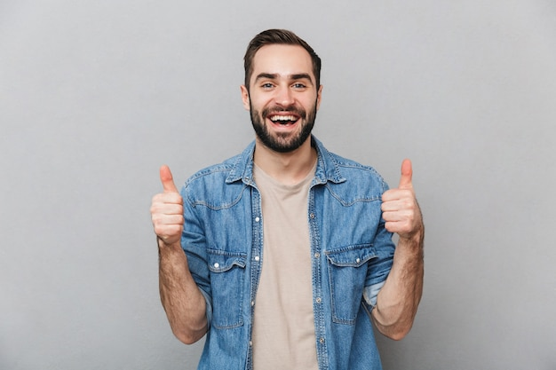 Excited cheerful man wearing shirt isolated over gray wall, showing thumbs up