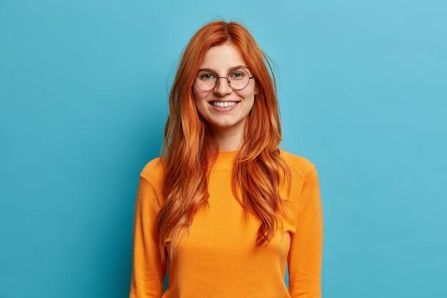 Eccitata donna rossa allegra con sincero sorriso a trentadue denti si diverte e guarda direttamente indossa occhiali da vista rotondi vestiti con un maglione arancione.