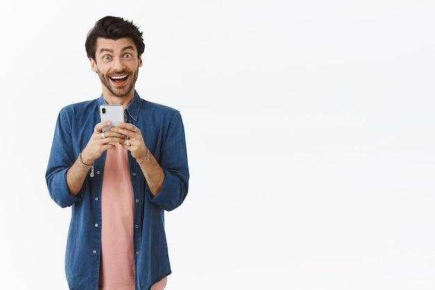 散らかったヘアカットで興奮した陽気な笑顔の男、スマートフォンを持って、海外の友人からオンラインでb-dayのお祝いを受け取り、幸せで興奮しているように見え、狂った白い壁のようにカメラにニヤリと笑う