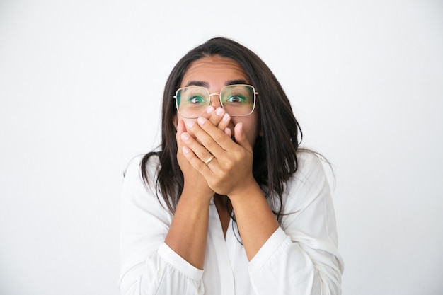 Excited cheerful woman in eyeglasses shocked with news