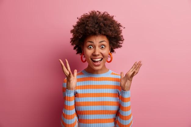 Возбужденная жизнерадостная женщина с афро-волосами держит руки поднятыми, слышит классные новости, получает неожиданный сюрприз, выражает радость и удивление, носит повседневный полосатый свитер, изолированный на розовой стене