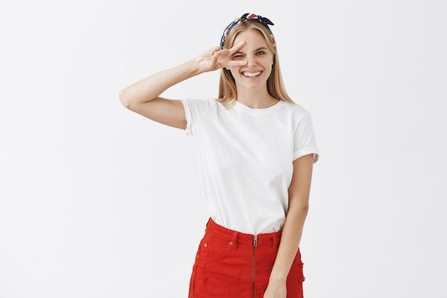 Возбужденная веселая молодая блондинка позирует у белой стены