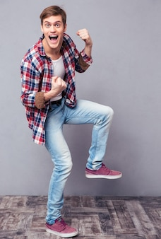 Excited cheerful young man in checkered shirt and jeans