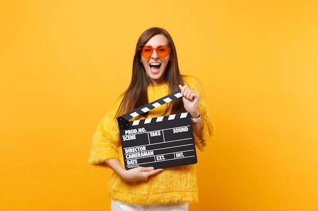 毛皮のセーター、黄色の背景で隔離のカチンコを作る古典的な黒のフィルムを保持しているオレンジ色のハートの眼鏡で興奮した陽気な若い女性。人々は誠実な感情、ライフスタイル。広告エリア。