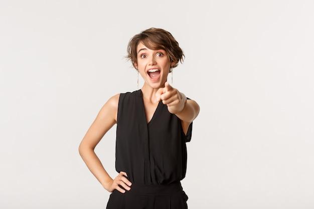 興奮した陽気な若い女性が喜んでカメラに指を向け、あなたを選んでいます。